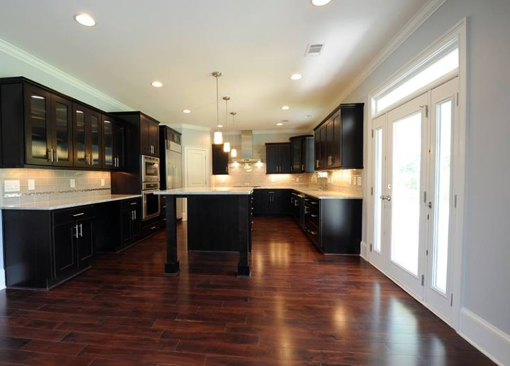 Light blue/gray with dark wide plank wood floors, black cabinets and large craftsman baseboards.