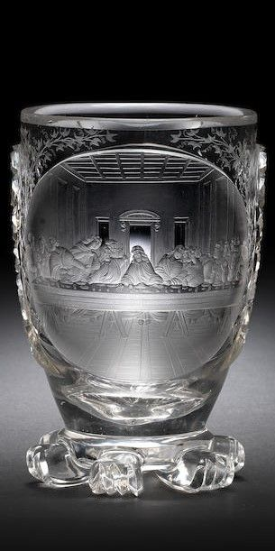A North Bohemian engraved beaker by Anton Simm, Gablonz, circa 1835 The ovoid bowl with a large circular panel finely decorated with a scene of 'The Last Supper', after Leonardo da Vinci, surrounded by delicate sprays of ivy, flanked on each side by tear-shaped motifs cut with hobnail diaper, the reverse with a large viewing lens, the base raised on six large cut bosses, 12.7cm high