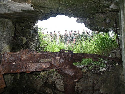 A heavy machine gun, possibly a Japanese Type 92 Heavy Machine Gun, lies abandoned in a bunker overlooking the landing beaches. There are still dozens of these bunkers all over the island. Most of them were destroyed during the battle. This pillbox still bore the scars of the fighting. It was marked with bullet holes and the inside was blackened. I imagine a flame thrower was used to clear this pillbox.(via)