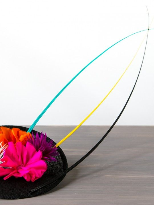 FRU-FRU   Black/Colour Hat/Fascinator Spring Racing   FORD MILLINERY  $420  Upturned black dented sinamay disc flaunts a vibrant pink silk flower with her clashing tangerine orange counterpart. Two spiky biot thistle arrangements – one of purple and one of white – site either side, strangely complimentary given their uncommon combination. Three ostrich quill spines of turquoise, yellow and black form to make a point – the hero of Fru-Fru's ensemble.