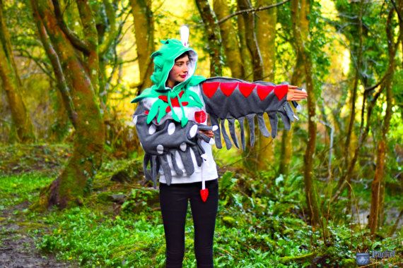 Dress like your favourite Pokemon with this hand-made Decidueye inspired hoodie!  Shiny Decidueye hoodie includes:  A highly detailed hoodie with the following high-quality details: -A blue-green hood with leafy feathers coming back from the front, and a green feathery ruff around the shoulders. -A pose-able white and red feather sitting atop the hood. -A red cross on the chest just below the hood opening. -Two green leaf-feathers hanging from the bottom of the hood. -A furry white chest…