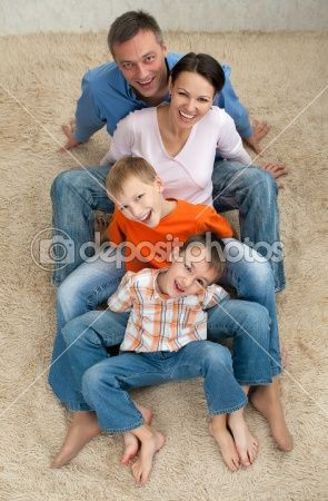 Family of four sitting on the carpet. I would like this way better on hay or straw.