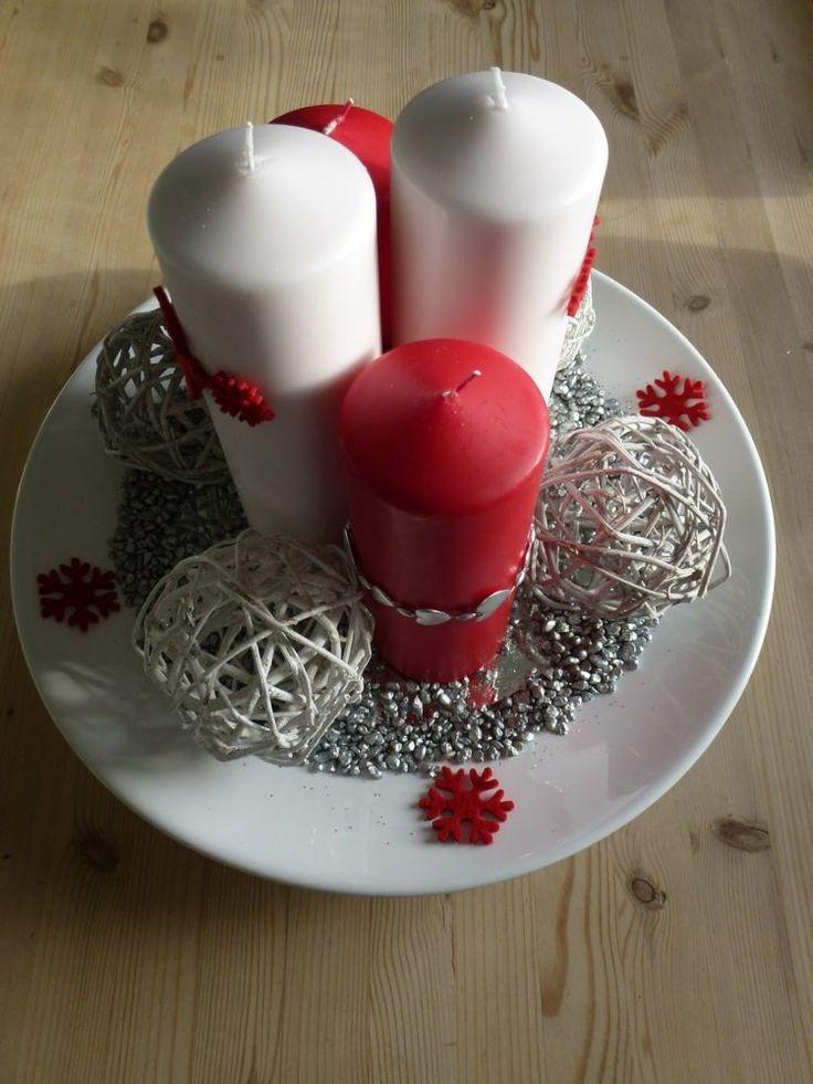 centre de table en bougies cylindriques rouges et blanches dans un plat rond décoré de boules en osier