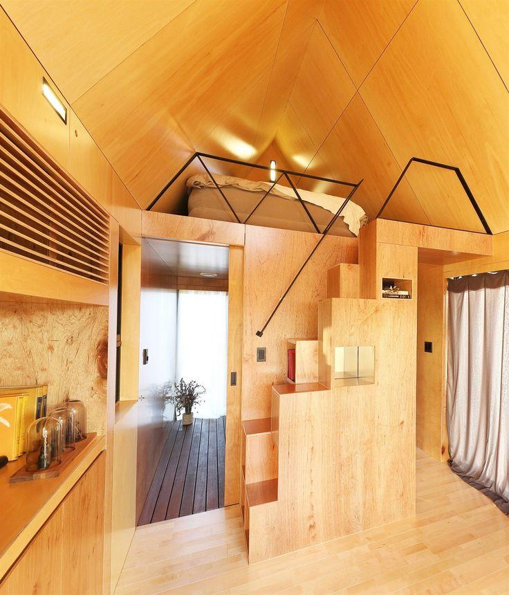 Schody vedou do spacího patra s lůžkem. Minimalistické černě lakované kovové zábradlí je tvořeno trojúhelníkovým vzorem, který kopíruje úhel střechy.