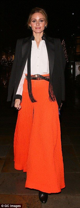 A bold look: All eyes were on Olivia in her bright orange maxi skirt, which she paired with thigh-high boots