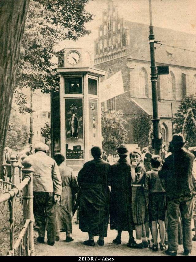"""Słup przy ulicy Świdnickiej, w tle kościół Bożego Ciała - podpis: """"We Wrocławiu zainstalowano na ulicach 100 głośników, umieszczonych w odpowiednich kioskach. Te publiczne stacje odbiorcze umożliwiają ubogiej ludności słuchanie audycyj propagandowych. Na zdjęciu grupy przechodniów przed głośnikiem w czasie przemówienia dra Goebbelsa czerwiec 1938"""