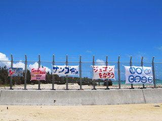 こうやって金網のフェンスで分断された砂浜が、日本にどれだけあるのだろうか。金網の向こうは69年続く米軍の占領地であり、中に入れば「日本の法律で罰せられます」と植民地のような看板が掛かっている。AK47を手にして戦っている世界各地の反米軍活動に比べれば、金網に貼られた横断幕や旗、リボンは実にささやかな抵抗だ。それすら我慢ならないという、米軍への卑屈かつ隷従的な精神構造をいい加減脱したいものだ。- 海鳴りの島から | 金網のフェンス1枚の向こうで行われていること