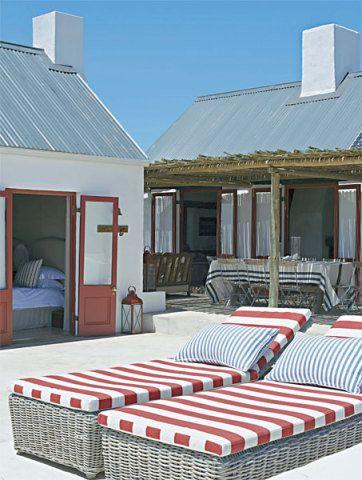O telhado metálico, comum nos celeiros sul-africanos, reverencia a arquitetura local. As esquadrias vermelhas são de okoumé, madeira regional de manejo sustentável