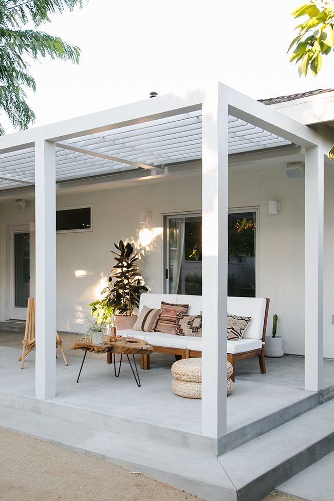 Simple, yet captivating patio in the calming shades of beige, brown and white covered with a pergola ready to embrace a climbing vine and make a wonderful canopy. Click on image to see more backyard patio ideas and porch designs (even on a budget).