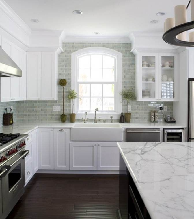 Dark floors, white cabinets, marble countertop, off gray backsplash.