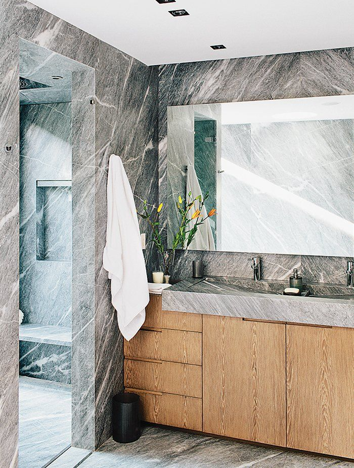 With a desire to create a home that could act as a reprieve from the bustle of Mexico City, Ezequiel Farcas created a #bathroom lined with a striking silvery-gray #marble. The spacious proportions and abundant natural light, along with a generously sized mirror and wood cabinets, break up the space.