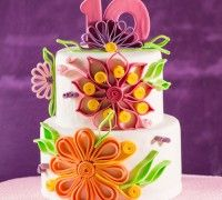Quilling is een prachtige techniek om taarten te decoreren. In dit recept hebben we deze feestelijke stapeltaart kleurrijk gedecoreerd met bloemen, bladeren en krullen.