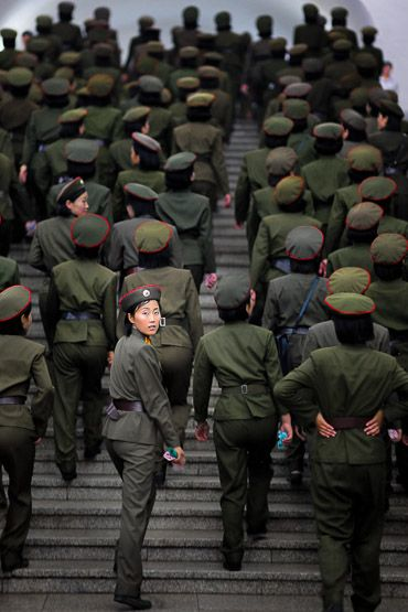 A curious female soldier look straight in the camera at the subway station. North Korea.