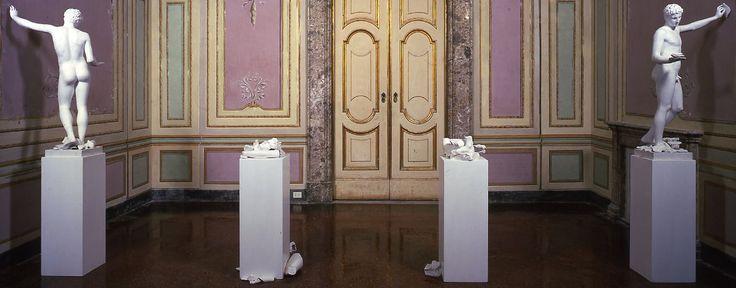 Giulio Paolini - L'altra figura - Gesso e legno dimensioni variabili. L'opera è composta da quattro o cinque basi di legno dipinto di bianco che squadrano lo spazio scenico dell'opera. Sui plinti più esterni, verso il muro, sono poste le copie in gesso dell'Efebo di Maratona; sostengono alcuni frammenti di un'altra copia, ridotta in frantumi.