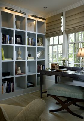 built-in bookcase wall with square cubbies = massive amounts of storage, exposed or hidden in a square basket that fits in the cubby