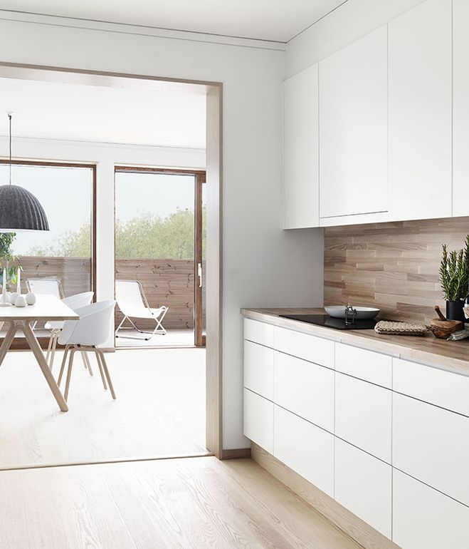 Horizontal wood planks in a light oak stain offer a natural contrast to the white cabinetry in this Swedish kitchen via folkhem.se. Photo...