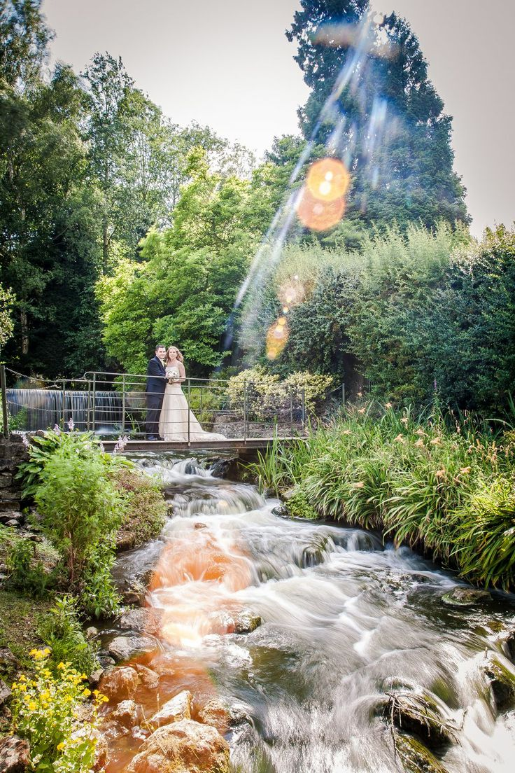 A sun-soaked photo of bride and groom on the bridge over the waterfall at The Orangery (photo re-edited in 2014)
