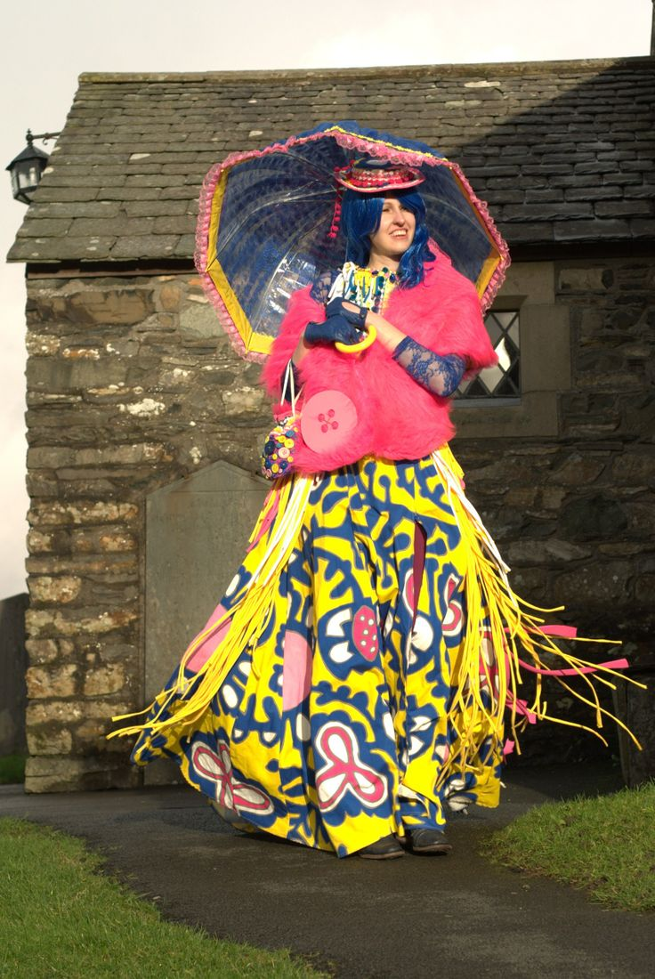 Yellow, blue and pink Victorian inspired pattern dress, featuring a bustle of multicoloured jersey strips, hat and lace parasol-umbrella. Photographed outside the church in Hawkshead, Cumbria. www.duxburydesigns.co.uk