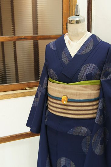 ネイビーの地に、カラフルな絣ストライプが形作る銅貨のような水玉モチーフが織り出されたウールの単着物です。