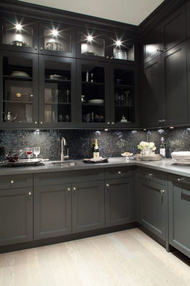 Gorgeous black kitchen design with oak wood floors, black shaker kitchen cabinets, gray quartz countertops and glass-front black glass tiles backsplash.  the lighting makes this too dark kitchen  amazingly inviting
