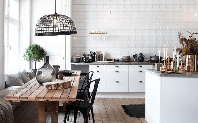 biała kuchnia z drewniana podłoga i stołem,skandynawska kuchnia z ażurowymi lampami z bambusa,kuchnia z jadalnią w skandynawskim stylu,białe płytki na scianie w kuchni,wiejski rustykalny stól w białej kuchni,czarne metalowe krzesła tonix w aranżacji białej kuchni