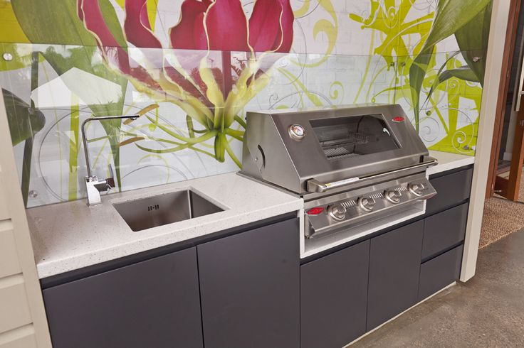 Modern Outdoor Kitchen / Built in BBQ Area using weather proof board, beefeater BBQ, colourful floral wallpaper with heat resistent glass splashback. Timber ceiling creates a warm welcoming atmosphere!