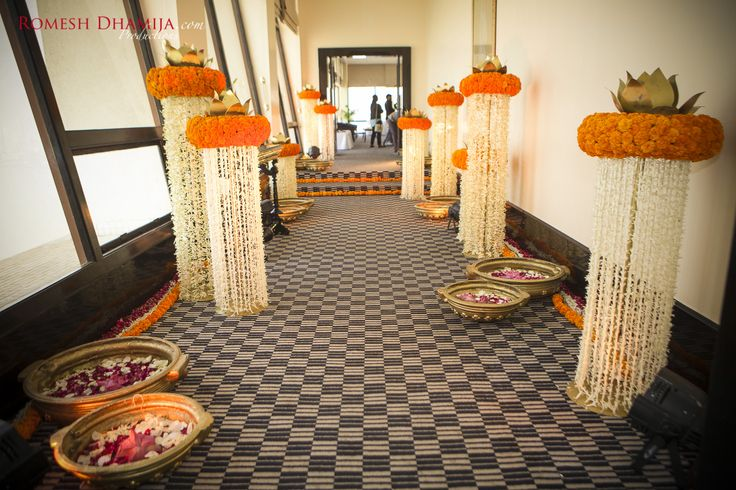 Love this entrance pathway adorned with hanging white flower elements with marigold top finished with Lotus Centrepieces and floral rangoli on the floor| Yellow & White Decor | Marigold & Jasmine | Floral Rangoli | Destination Weddings | RDP