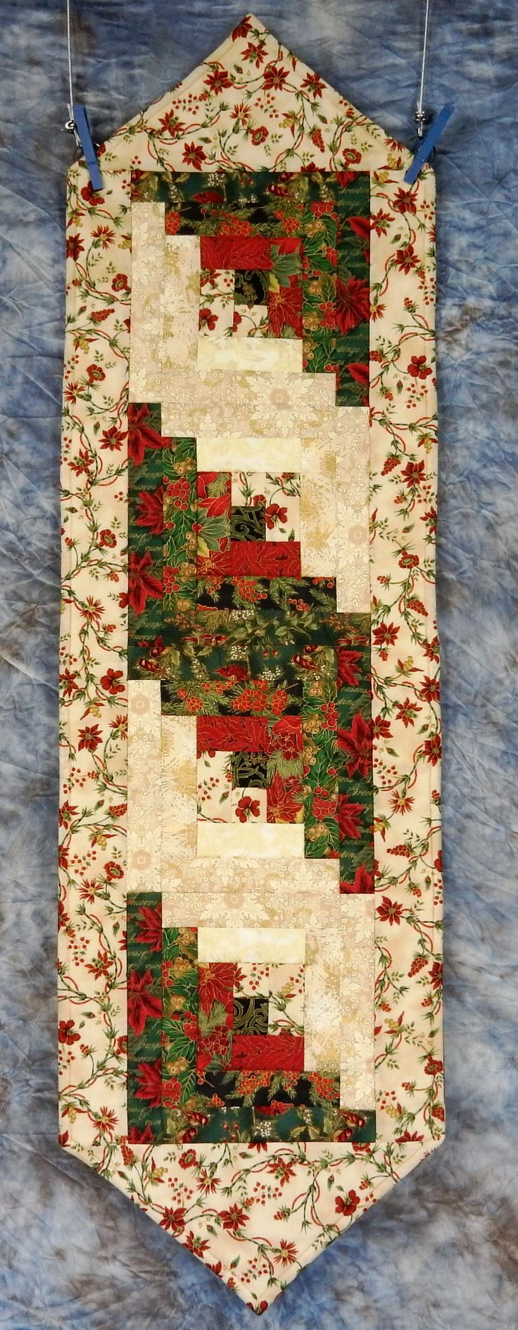 This beautiful, quilted table runner contains four log cabin quilt blocks composed from gorgeous Holiday fabrics. Backing for the runner is Seasons Greetins making the runner reversible and appropriate for use throughout the winter and holiday season. It is machine pieced and machine quilted. The table runner measures 14.5 x 50 with tapered ends. This runner is washable and instructions will be sent with your purchase. Fabric supplies from Jordan Fabrics of Oregon.
