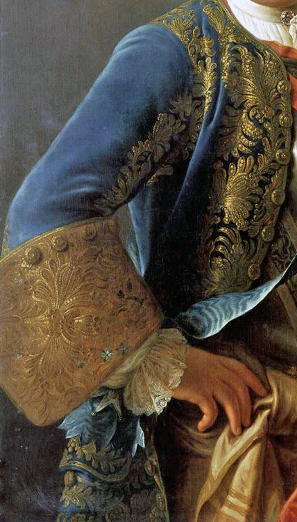 Cuff. Also, trim at sleeve seam.  Blue velvet frockcoat with elaborate gold embroidery to front panels that extends the length of the sleeve to enormous cuff upturned to elbow of heavy gold thread (possibly separately attached), matching gold buttons on cuff and frockcoat. Silk sash tied around waist. Detail from portrait of King Augustus III of Poland, 1755.