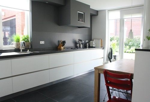 The modern family kitchen boasts contemporary appliances and clean lines. A charcoal gray accent wall creates a sleek backdrop and smooth connection with the Brazilian slate floor tiles. Red accessories, such as a modern high chair from Stokke Tripp Trapp, contrast well with the combination of gray, white and light wooden furnishings.