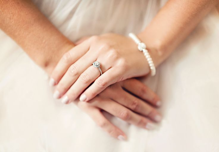 Delicate white gold and diamond halo engagement ring and pearl bracelet | Bride hand photo on ballgown | Photography: Melissa Avey