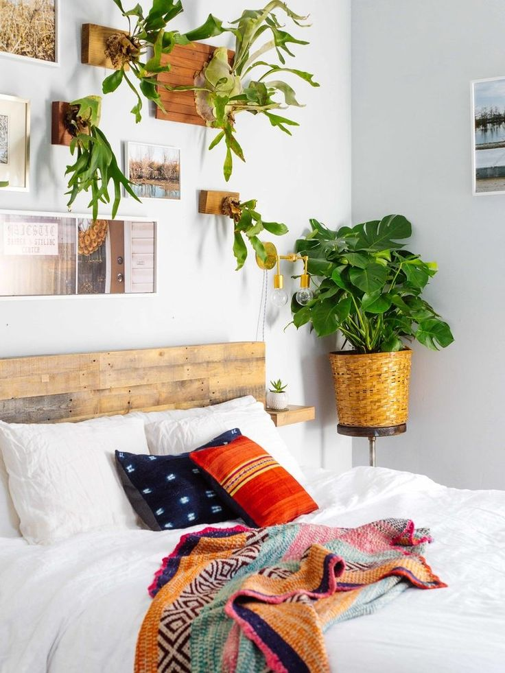 Using plants on the wall with layers of global fabric to give a wonderful boho look to your bedroom