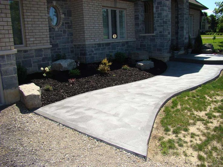 Coloured, textured concrete sidewalk adds great curb appeal to this upscale home.