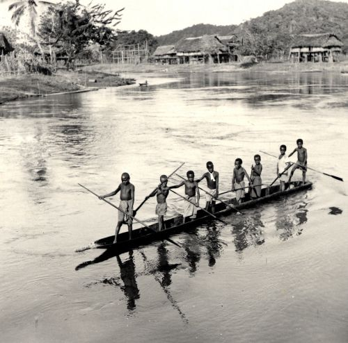Eight people standing in a canoe spear fishing on the Sepik River. Huts on stilts in background.