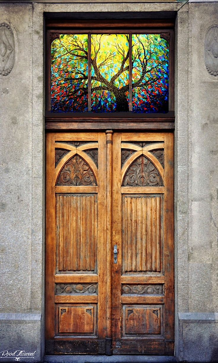 Stained glass over a carved wooden door (location unknown)
