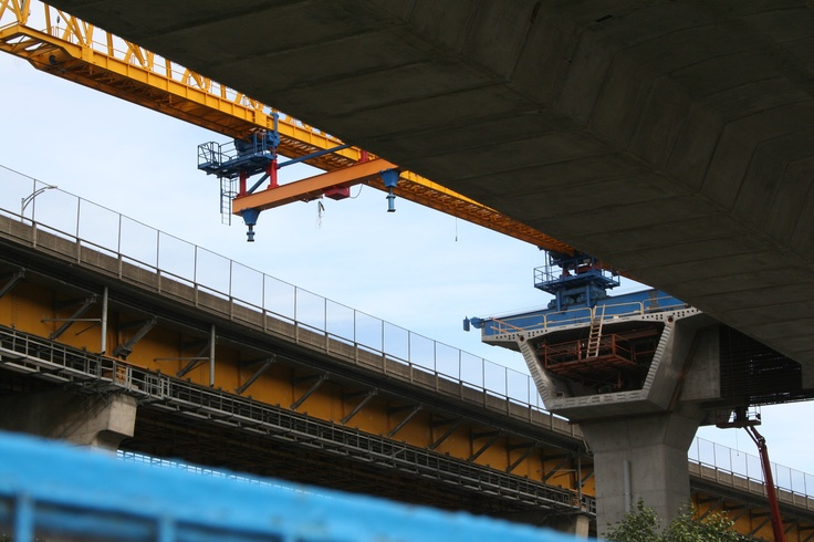 "The travelling gantry crane viewed from underneath. A section of ""rocks"" needs to be attached to the exposed pillar here but the deck of the existing Port Mann Bridge encroaches on the required path here."
