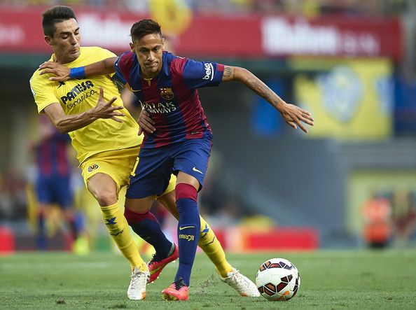 Neymar Jr of Barcelona is tackled by Bruno Soriano (L) of Villarreal during the La Liga match between Villarreal CF and FC Barcelona at El Madrigal stadium on August 31, 2014 in Villarreal, Spain.