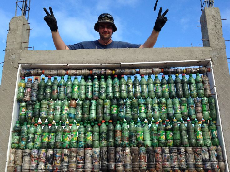 Me standing behind an upper portion of a bottle school wall that I worked on