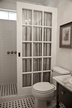 Repurposed old French pocket door in place of a glass shower enclosure for a…