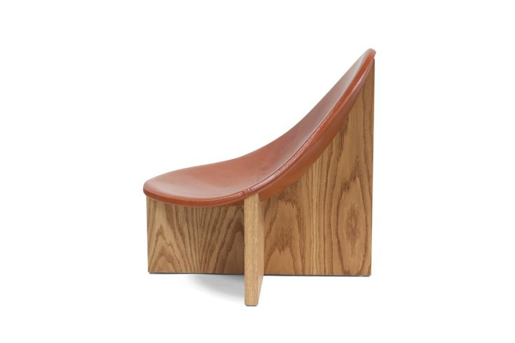 """A striking and sculptural accent chair, the Nido Chair is an elemental interpretation of a bird's nest. Meaning nest in Spanish, the """"Nido"""" chair was designed out of a juxtaposition of shapes. An egg-like upholstered seat is nested in a cross-shaped solid wood frame. The strong lines of the base in either walnut or white …"""