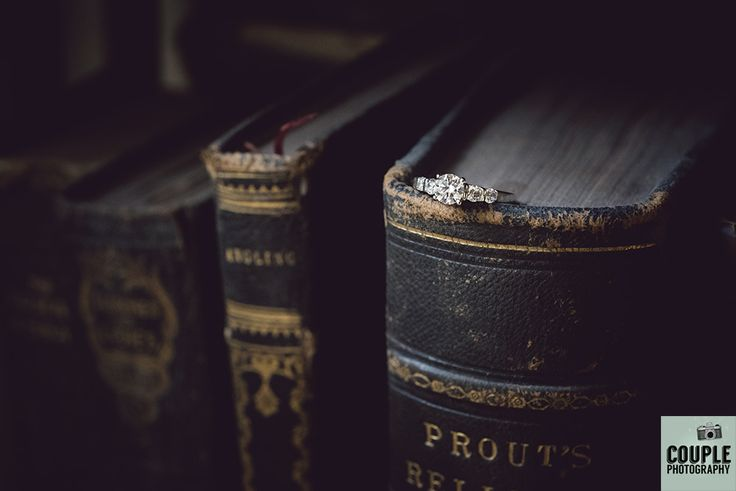 The bride's diamond engagement ring sits on some old books. Weddings at Tankardstown House by Couple Photography.