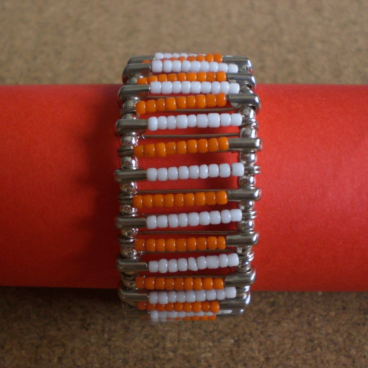 Bracelet made using safety pins with orange and white plastic beads. Connected with silver round beads.