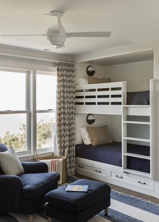 Transitional boys' room with nautical wall sconces illuminating built in bunk beds with a built-in ladder dressed in navy bedding topped with white and beige pillows beside windows dressed in blue chevron curtains next to a navy chair and ottoman on caster legs atop a striped blue rug.