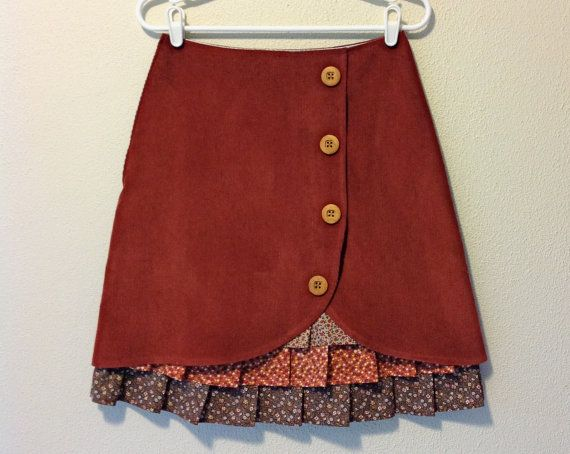 This sweet skirt is made out of a rust orange, wide wale corduroy. It is cut into an overlapping tulip shape in the front to reveal layers of ruffles made out of vintage, calico cottons in cream, orange, brown and yellow. The ruffles are attached to a polyester lining. Four wooden buttons climb up the front to the waistband. The skirt zips up the side.  This skirt has a 28 waistband and will fit up to 37 hips, so about a size 2 21 long  Machine washable