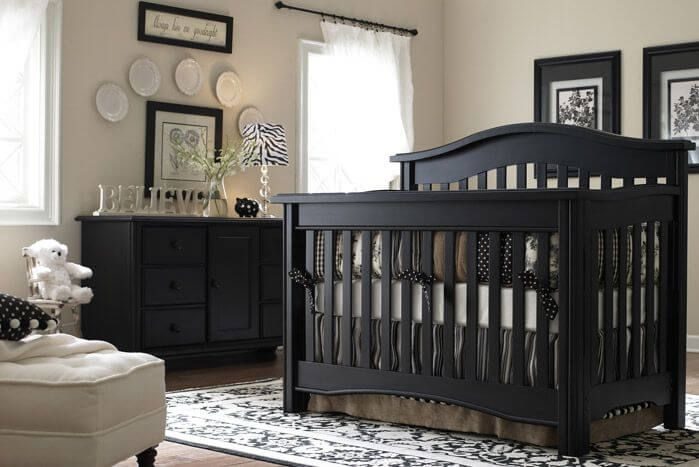 Black and white theme is exemplified by zebra-shade lamp at center of this nursery, with dark wood crib standing over black and white patterned rug on hardwood flooring. Dark wood dresser and picture frames on walls match the crib.