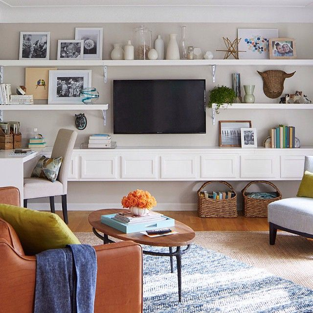 White corner-to-corner shelves and cabinets in the living area create design impact. Use stock upper kitchen cabinets to provide a custom storage look without custom costs. The open shelves are simple in design and installation. Intimate seating pulls furniture away from the walls while a neutral rug anchors the grouping. An accent rug picks up the recurring blue. Click the link in profile for the #DIY Media Wall! #Lowes #LivingRoom #BuiltInShelves #MediaWall