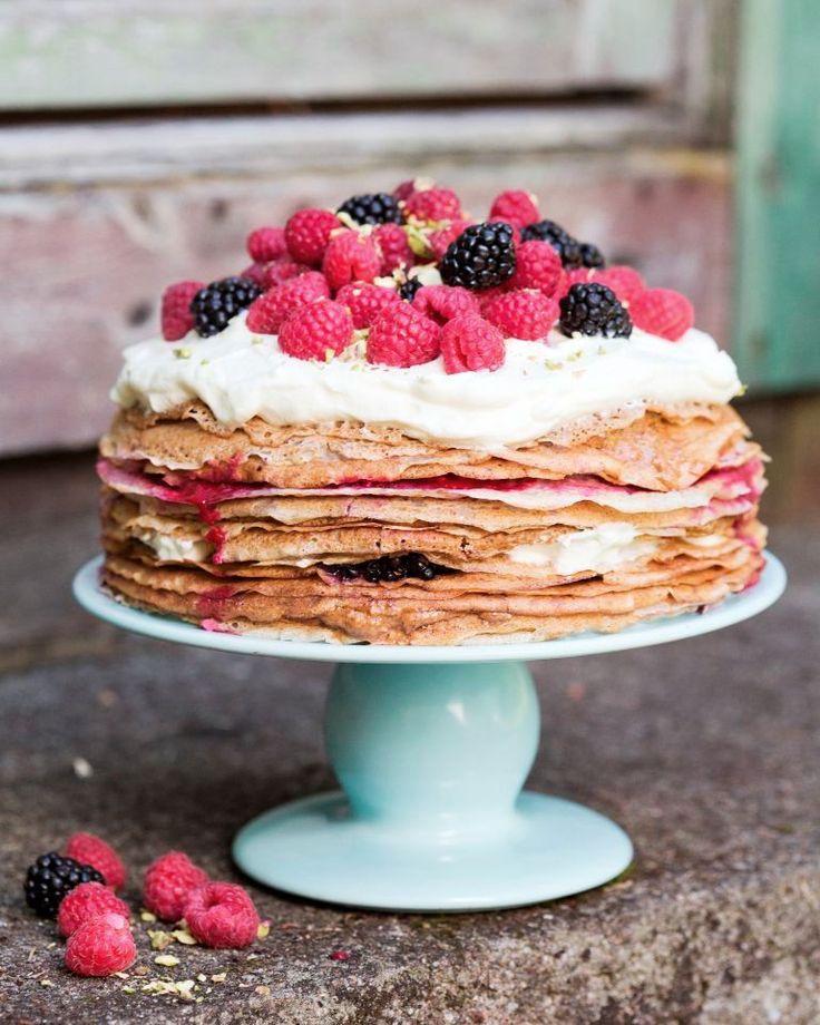 """Um bolo lindo, com todas as panquecas sobrepostas e os frutos vermelhos e as natas sobressaindo pelos lados. Uma criação de David e Luise, autores do livro """"Vegetariano Todos os Dias"""""""