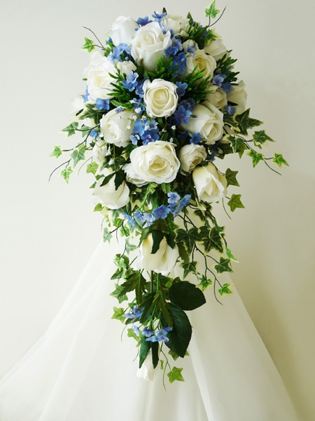 Traditional shower bouquet featuring a mass of trailing ivy, warm white roses, and forget-me-nots.