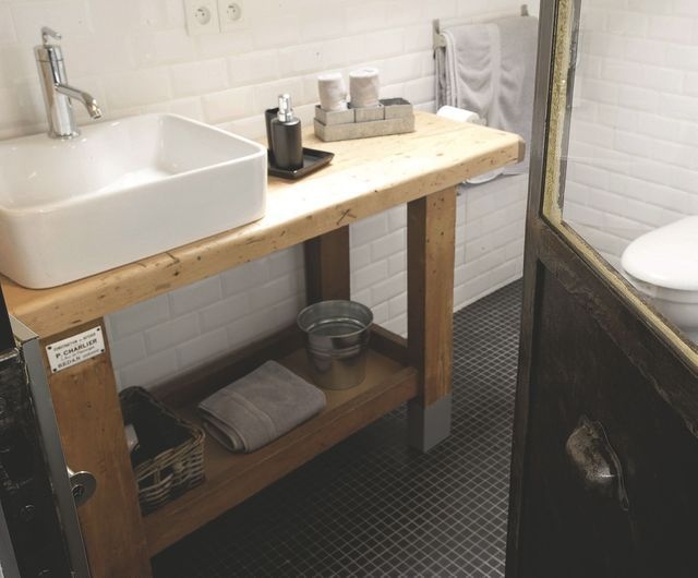 Un établi d'atelier relooké en meuble de salle de bains Comment ? Nettoyage à l'eau savonneuse - Réparer les fissures à la pâte à bois et poncer - Installer la vasque - Appliquer 2 couches de vernis spécial salle de bains.