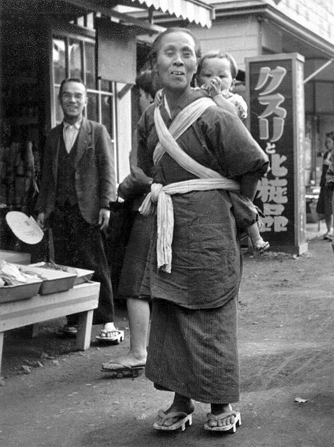 Elderly Japanese woman with baby on her back. Man watching. Undated black-and-white photograph.